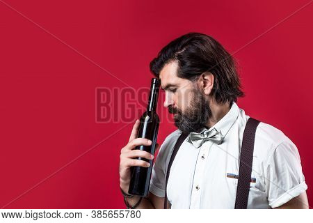 Handsome Bearded Rich Man With Stylish Hair Mustache And Beard In Suspenders Holding Bottle Of Wine,