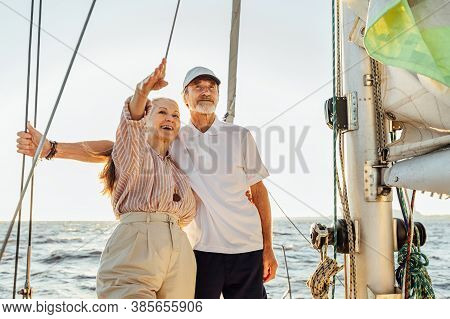 Senior Couple Enjoying The View On Private Sailboat. Retired People Standing Together On Yacht At Se