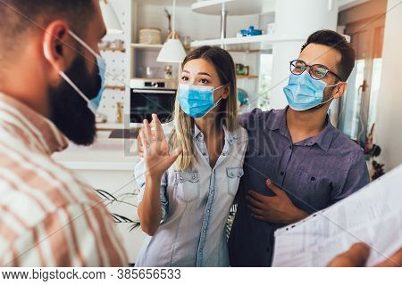 Young Happy Married Couple In Medical Masks Standing In The New House With Male Real-estate Agent. P