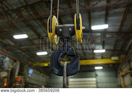 Selective Focus Close Up View Of Lifting Hook With Safety Latch Attached To Sheaves Suspended By Wir