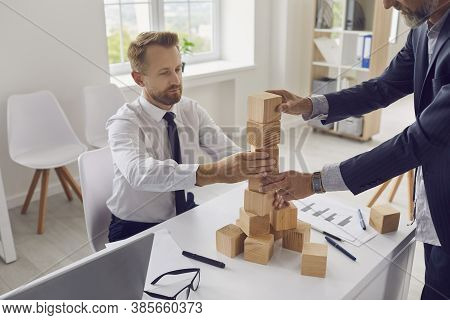 Entrepreneurs Of Different Generations Building Tower Together As Metaphor For Business Succession