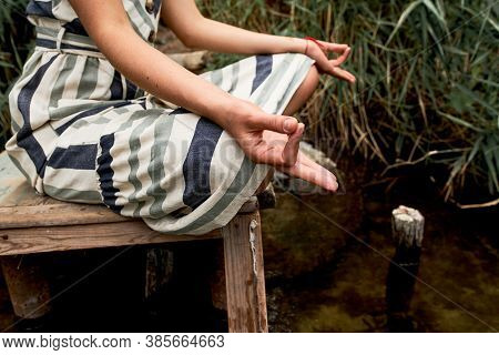 Young Woman In Dress Meditating On The Nature. Summertime, Mind Detox And Yoga Concept