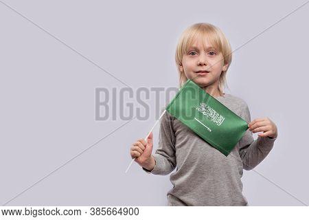 Serious Blond Boy Holding Flag Of Saudi Arabia. Education In Saudi Arabia.