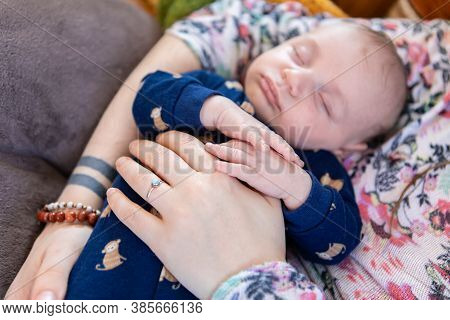 Selective Focus Shot Of Young Infant Boy Snoozing In The Arms Of His Mother, Her Hand Adorned With A