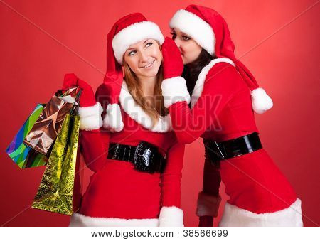 two happy young Santa girl talking over red background . poster