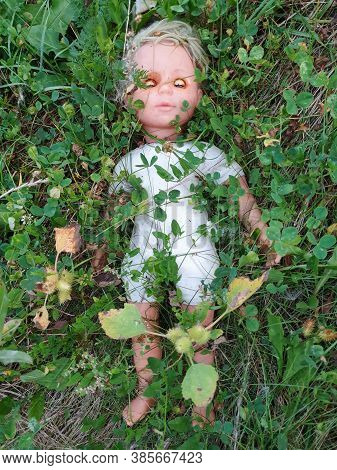 Sad Childhood Forgotten Memory Concept Doll In Grass. Time Passes And Childhood Is Left Behind With
