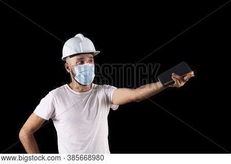 Young Hispanic Male Construction Worker With Mask Estimating A Measurement