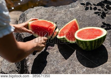 Shot From Behind Of A Woman Slicing A Juicy, Ripe Watermelon In Chunks And Slices On A Rock By The B