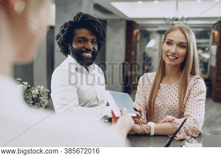 Business Trip Concept. Black Man And Caucasian Woman Businesspeople Colleagues Checking-in In Hotel