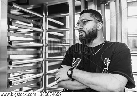 Black And White Portrait Of A Man In The Backlight Near The Turnstile