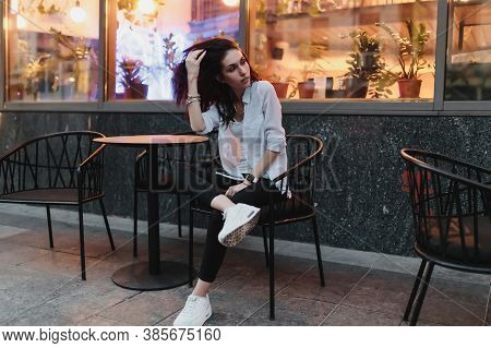 Young Woman Sitting At A Table On The Street In The Evening.
