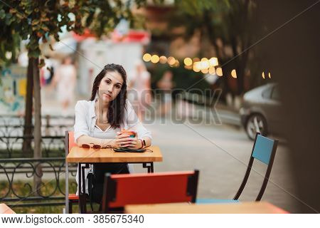 Woman Sitting At A Table On The Street. Evening Warm City.