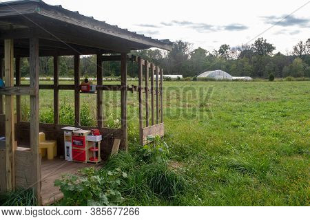 Rustic Clubhouse With Toys Sits In Green Agricultural Field On Organic Family Farm With Rural Landsc
