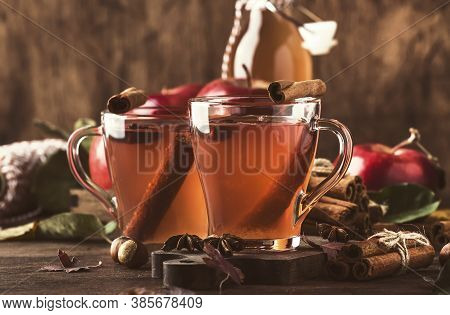 Hot Mulled Apple Cider Vinegar With Cinnamon Sticks, Cloves And Anise On Wooden Background. Traditio
