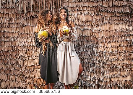 Two Beautiful Young Stylish Fashion Models Having Fun With Coconuts Outdoors