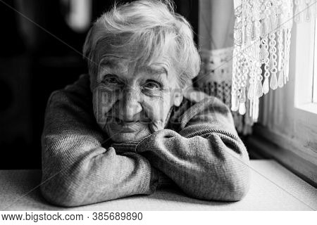 An old woman looking at the camera. Black and white photography.