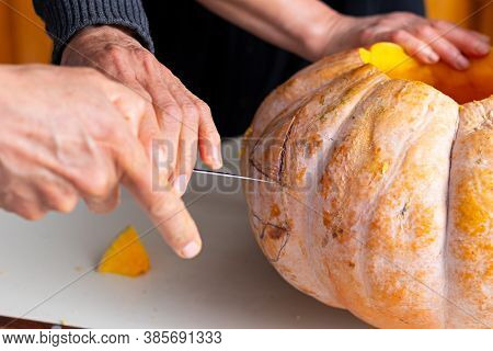 Hands Of A Couple Carving A Pumpkin At Decorated Kitchen In Halloween