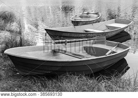 Rowboats Are At Coast Of A Still Lake, Black And White Photo