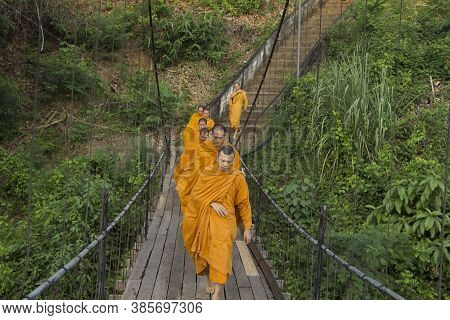 An Old Wooden Bridge That Crosses The River In The Countryside Where Many Monks Are Crossing.-thong