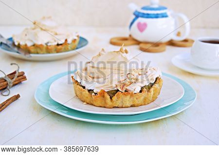 Mini Tarts With Custard, Gooseberries And Meringue On A White Plate On A Light Concrete Background.