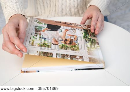 Close Up. A Woman Flips Through A Photo Book From A Family Pregnancy Photo Shoot. Beautiful And Conv