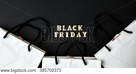 Wooden Letters Text Black Friday With Packaging Bags In Front Black Background, Copy Space, Banner T