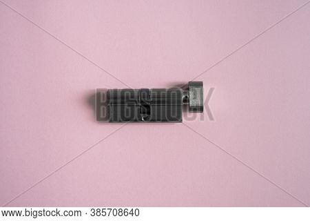 A Door Lock Cylinder Core On The Pink Background. The Cylinder Of The Lock. Installing A New Lock On