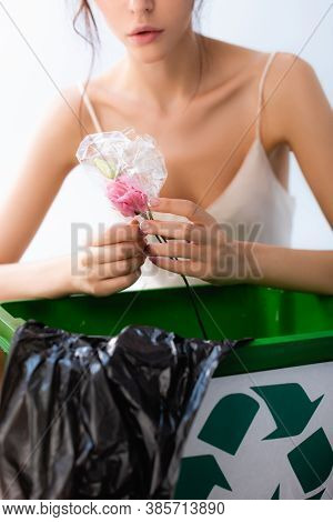 Partial View Of Woman Holding Flower In Wrap Near Trash Can With Recycle Sign And Plastic Bag Isolat