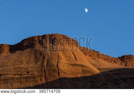 Sun Lowers In Clear Blue Sky And Brightens A Red Rock Escarpment Under White Moon