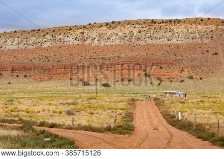 Utah Landscape With Huge Mesa Landform Dominating Small Buildings And Dirt Road Running Two Directio