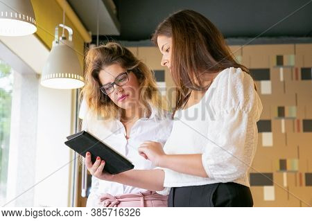 Attractive Female Designers Watching Projects On Screen. Brunette Woman Holding Tablet And Showing S