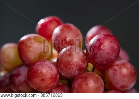 Bunch Of Red Grapes On A Black Background With Water Drops