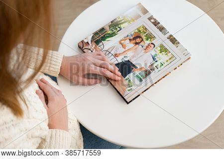 A Pregnant Woman Flips Through A Photo Book From A Family Pregnancy Photo Shoot. Beautiful And Conve