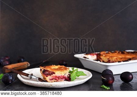 Vanilla Muffin With Plums And Mint On A Dark Concrete Background. Fruit Pie.