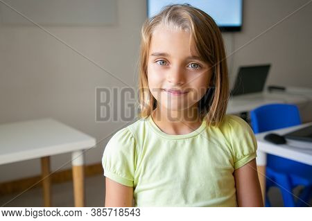 Portrait Of Blonde Pretty Girl In Yellow Shirt. Lovely Caucasian Kid Posing In Classroom After Lesso