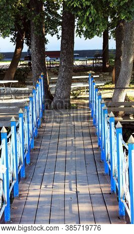 Wood Bridge With Wrought Iron Blue Railings Across The River