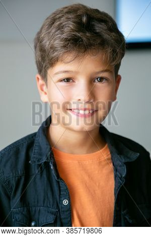 Portrait Of Caucasian Little Boy With Stylish Haircut. Cute Happy Child Posing In Classroom After Le