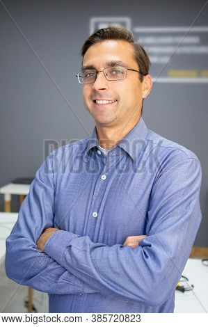 Portrait Of Caucasian Content Teacher With Folded Hands. Middle-aged Handsome Man In Glasses Posing