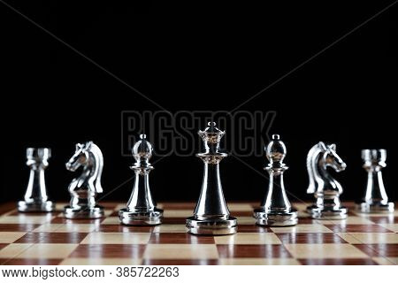 Shiny Steel Chess Figures Standing On Wooden Chessboard. Intellectual Duel And Tactical Battle Symbo