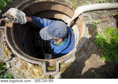 Worker Cleans The Sewer Hatch.a Worker Cleans A Sewer Hatch. A Man In The Hatch.