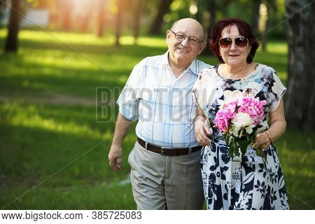 Happy Elderly Couple. Handsome Man And Woman Senior Citizens. Husband And Wife Of Old Age For A Walk