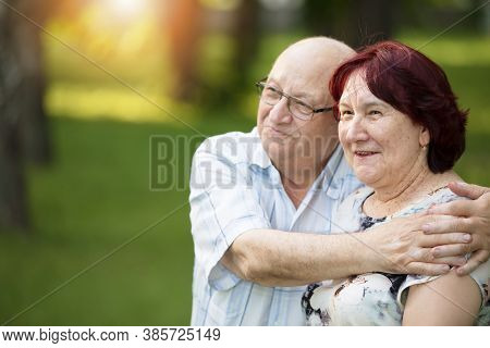 Happy Elderly Couple On A Walk. Handsome Man And Woman Senior Citizens. Husband And Wife Of Old Age