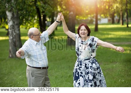 Happy Elderly Couple Dancing. Handsome Man And Woman Senior Citizens. Husband And Wife Of Old Age Fo