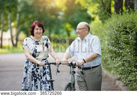 Happy Elderly Couple With A Bicycle. Handsome Man And Woman Senior Citizens. Husband And Wife Of Old