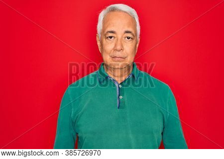 Middle age senior grey-haired man wearing casual sweater over red isoalted background with serious expression on face. Simple and natural looking at the camera.