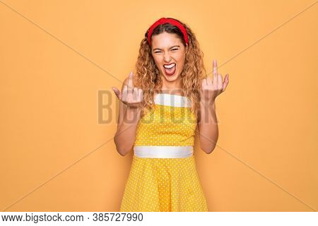 Beautiful blonde pin-up woman with blue eyes wearing diadem standing over yellow background Showing middle finger doing fuck you bad expression, provocation and rude attitude. Screaming excited