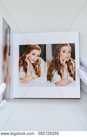 Hands In White Gloves Flipping Through A Photo Book With Wedding Photos. Beautiful And Convenient St