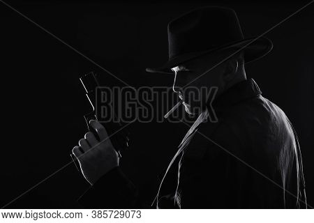Old Fashioned Detective With Gun Smoking Cigarette On Dark Background, Black And White Effect