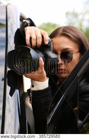 Private Detective With Camera Spying Near Car Outdoors