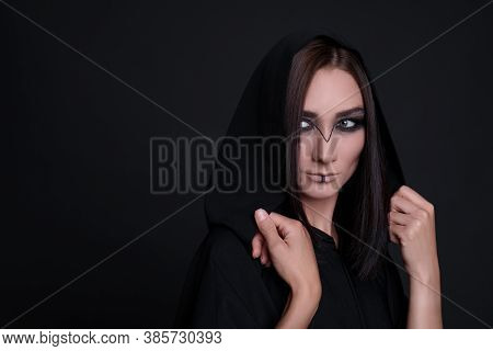 Mysterious Witch In Mantle With Hood On Black Background. Space For Text